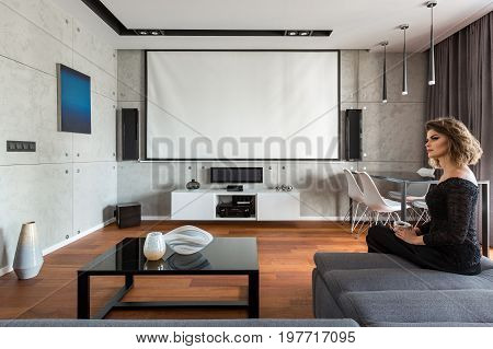 Woman sitting on sofa in living room with black coffee table and projector screen