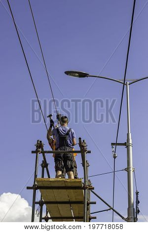 Workers Installing The Overhead Power Line Equipment