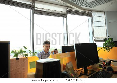 Young man in smart casual wear holding smart phone and looking at it while sitting at his working place in office