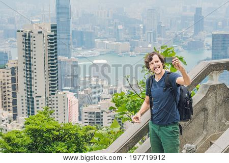 Hong Kong Victoria Peak Man Taking Selfie Stick Picture Photo With Smartphone Enjoying View Over Vic