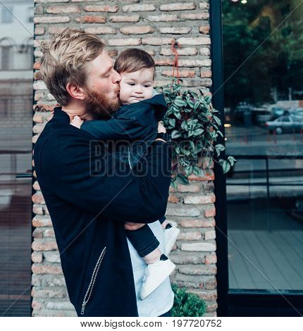 Dad with a small son in his arms against the wall on the street