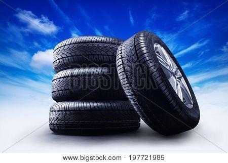 four car wheels under a blue sky