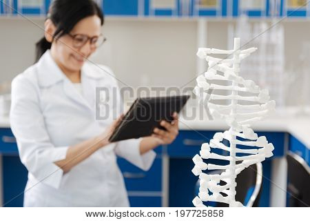 Human DNA. Selective focus of a DNA model with a nice professional female scientist working in the background