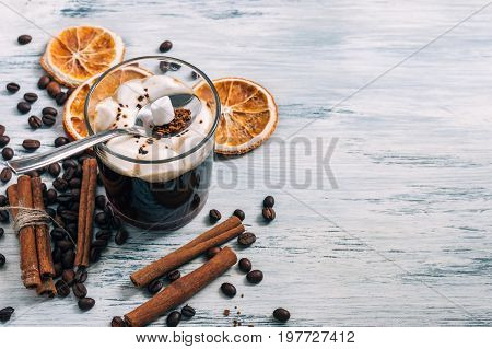 Hot chocolate with marshmallows near a grain of coffee and a slice of dried orange