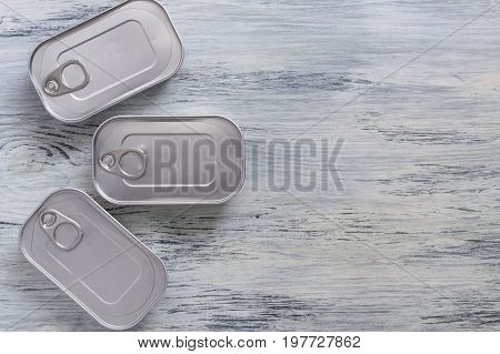 Cans on a wooden background. Three cans of canned food on a table