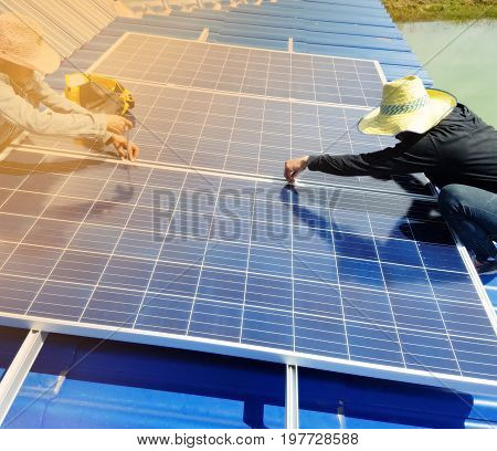 Workers installing alternative energy photoSolar panels on roof.