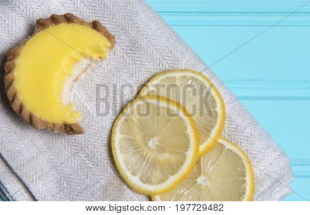 Lemon cake with a bite missing, taken on a blue background with copy space