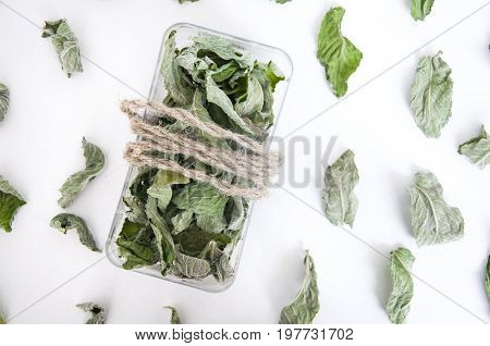 Dry green leaves of mint and melissa in a plastic box with rope and on white background. Close up, top view.