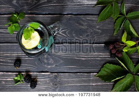 Summer drink with blackberries, lemon and mint in a glass jar on a dark rustic wooden background with copy space top view.