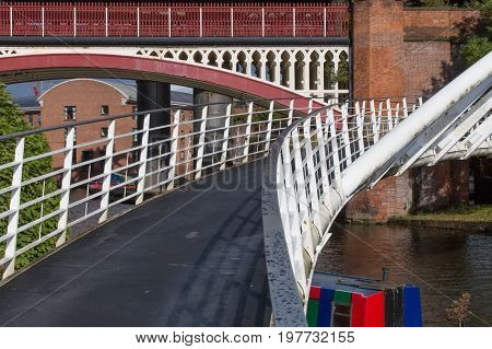 The modern Merchant's Bridge in Castlefield Basin with the historical Victorian Rail Viaduct behind.