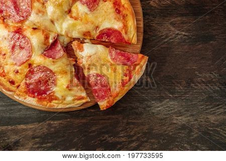 An overhead photo of a pepperoni pizza with a slice cut off, shot from above on a dark rustic texture with a place for text