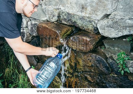 young man fill up the bottle from water source in mountains