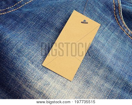 Blank label price tag on jeans from recycled paper. Mock-up for price or brand presentation.
