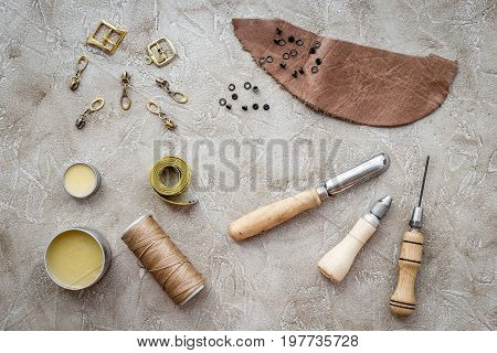 Leather craft. Tanner's tools on grey stone background top view.