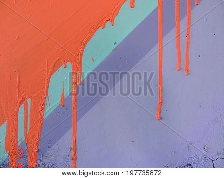Concrete colored purple wall with orange paint streaks texture.