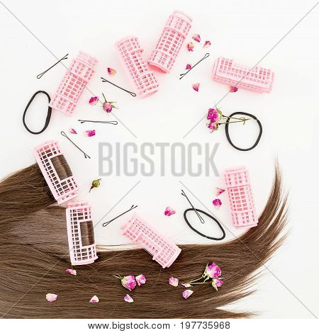 Hairs and women's curlers, stylish concept on white background. Flat lay. Top view.