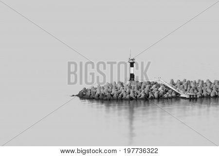 Lighthouse on edge of breakwater in Sochi sea port.