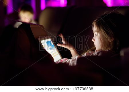 Two Adorable Little Sisters Playing With A Digital Tablet In A Dark Room