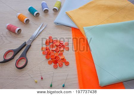 Tools for sewing for hobby set on wooden table background top view. Sewing kit. Thread needles and cloth. tailor workspace with sewing and handmade tools