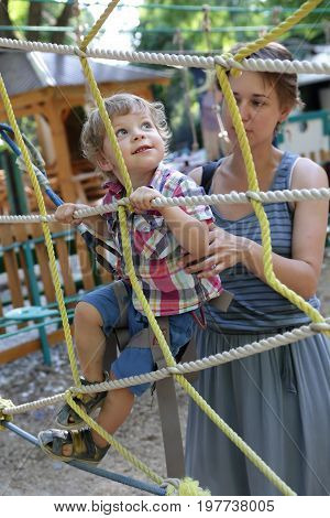 Mother helps her son on obstacle course