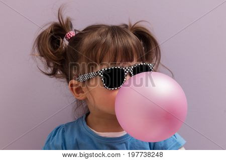 Little girl with sun glasses blowing up pink chewing gum against a light purple background
