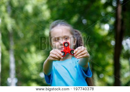 Little girl playing with a red spinner in summer day