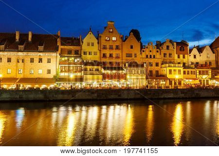Buildings of the old town Gdansk reflected in a water in evening