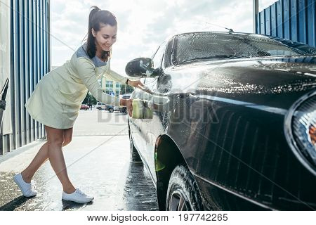 Young woman hands cleaning car by yellow sponge on carwash