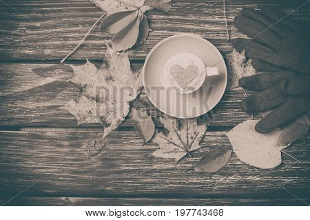 Autumn Leaves,gloves And Coffee Cup On Wooden Table.