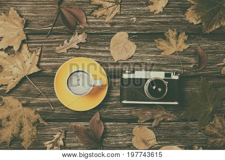 Autumn Leaves, Camera And Coffee Cup On Wooden Table.