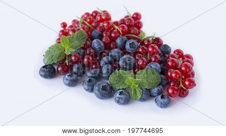 Ripe blueberries and red currants with mint. Berries at border of image with copy space for text. Background berries. Various fresh summer berries on blue background.