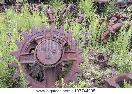 Rusting Gears In Green Field