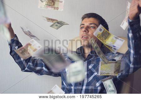 young man businessman among flying banknotes(euros rubles dollars)