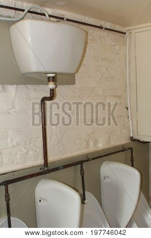 Old Fashioned High Level Cistern Feeding Into Urinals In A Run Down Gents Toilet Or Rest Room