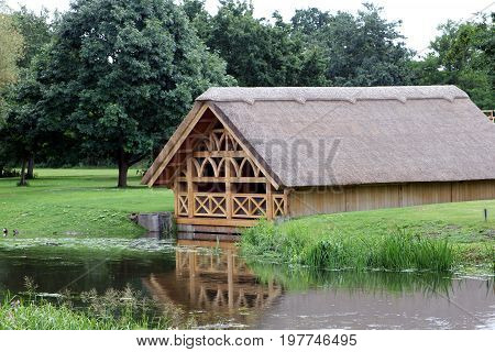 Pretty Tudor Style Wooden Framed Thatch Boathouse In A Wood On The Edge Of A Lake Or River