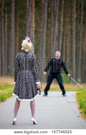 Young Woman Holds The Gun In Hand Against The Maniac In The Wood