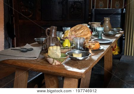Rustic Old Wooden Dining Table In A Medieval Cottage, Laid With Bread, Meat, Cheese And Fruit, And A