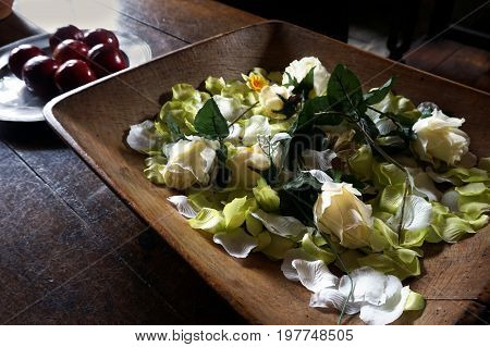 Wooden Bowl Of Artificial Rose Flowers And Leaves, On An Old Wooden Table, In Natural Daylight