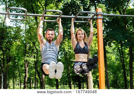 Young sportive woman and bearded man doing pull-ups exercises on crossbar in a parrk at summer day.