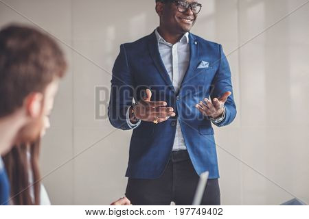 Confidence and charisma. Cheerful young African man in full suit at meeting