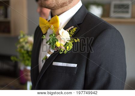 groom in suit with yellow bowtie ..
