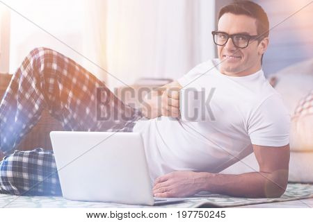 Look at me. Handsome young brunette holding cup in right hand keeping his left hand near laptop while expressing positivity