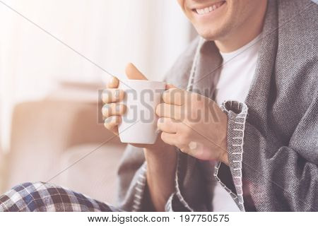 Be healthy. Delighted male keeping white cup in both hands warming himself with hot drink while sitting covered in plaid