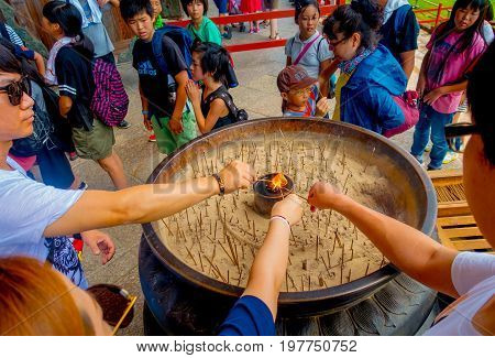 Nara, Japan - July 26, 2017: Unidentified people with incense in their hands at ther enter of Todai-ji Temple. This temple is a Buddhist temple located in the city of Nara, Japan.