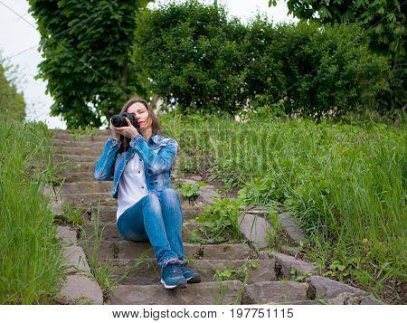 Beautiful girl tourist in a cotton jacket sits on vintage stone steps and taking photos with a professional camera in windy weather.