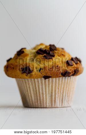 Tasty homemade vanilla muffin with chocolate chunks on bright white background. Closeup.