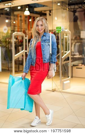 Concept Shopping. Portrait of beauty blonde smiling woman in casual holding shopping bags near shop in the shopping center. Indoor