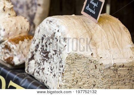 Big piece of nougat with honey and hazelnuts. France Montelimard