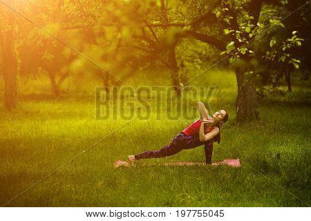 Yoga practicing in morning garden. Young female practicing extended side angle pose with twist. Utthita Parsvakonasana. Toned image.