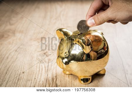 Putting A 50 Cents Of Dollar Coin Into A Piggy Bank